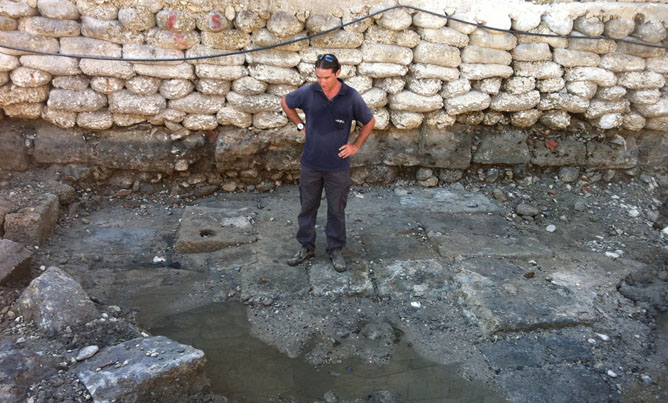 A member of the Israel Antiquities Authority standing on the ancient quay that was exposed in Acre. (Photo: Kobi Sharvit/IAA)