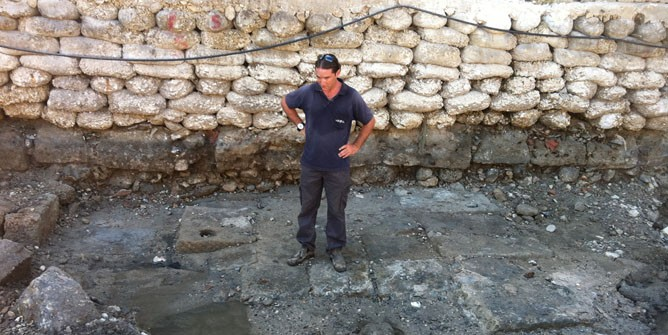A member of the Israel Antiquities Authority standing on the ancient quay in Acre. (Photo: Kobi Sharvit/IAA)