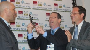 Shaul Tzemach, Director General of the Ministry of Energy and Water, looks on as Dr. Amit Mor, Co-CEO of Eco Energy, presents Yosef Abramowitz, President of Arava Power Company, the 2012 Energy and Business Convention Person of the Year Award. (Hannah Schafer)