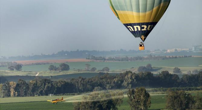 A hot air balloon flies over the Israeli countryside. Photo by Moshe Shai/Flash90.