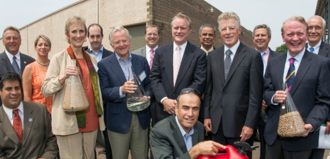 Primus Green Energy Chairman Dr. Yom-Tov Samia (front middle) with guests including former New Jersey Governor Jim Florio at the company's demo plant dedication. The beakers contain wood pellet feedstock and Primus' 93-octane gasoline.