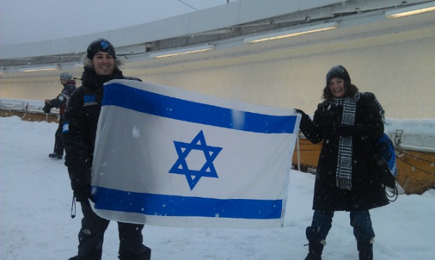 Israeli Bobsleigh and Skeleton Federation CFO Philip Nathan and Chana Anolick hoist the Israeli flag near the end of the track.