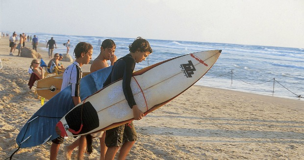Surfers on the beach in Haifa.