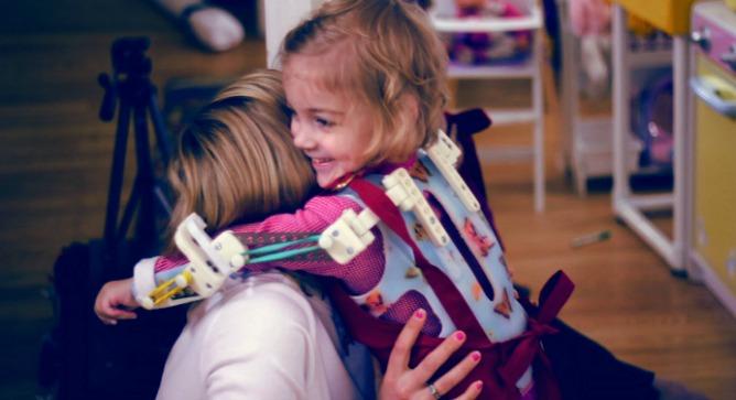Emma using her Magic Arms printer-made exoskeleton.