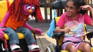 The Israeli muppet, Sivan, plays with a girl who also uses a wheelchair in Friendship Park.