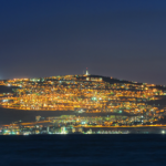 The city of Tiberias lights up the nighttime shore of the Kinneret.