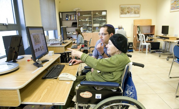 "A Yad Sarah ""angel"" teaching a pensioner how to use the Internet."
