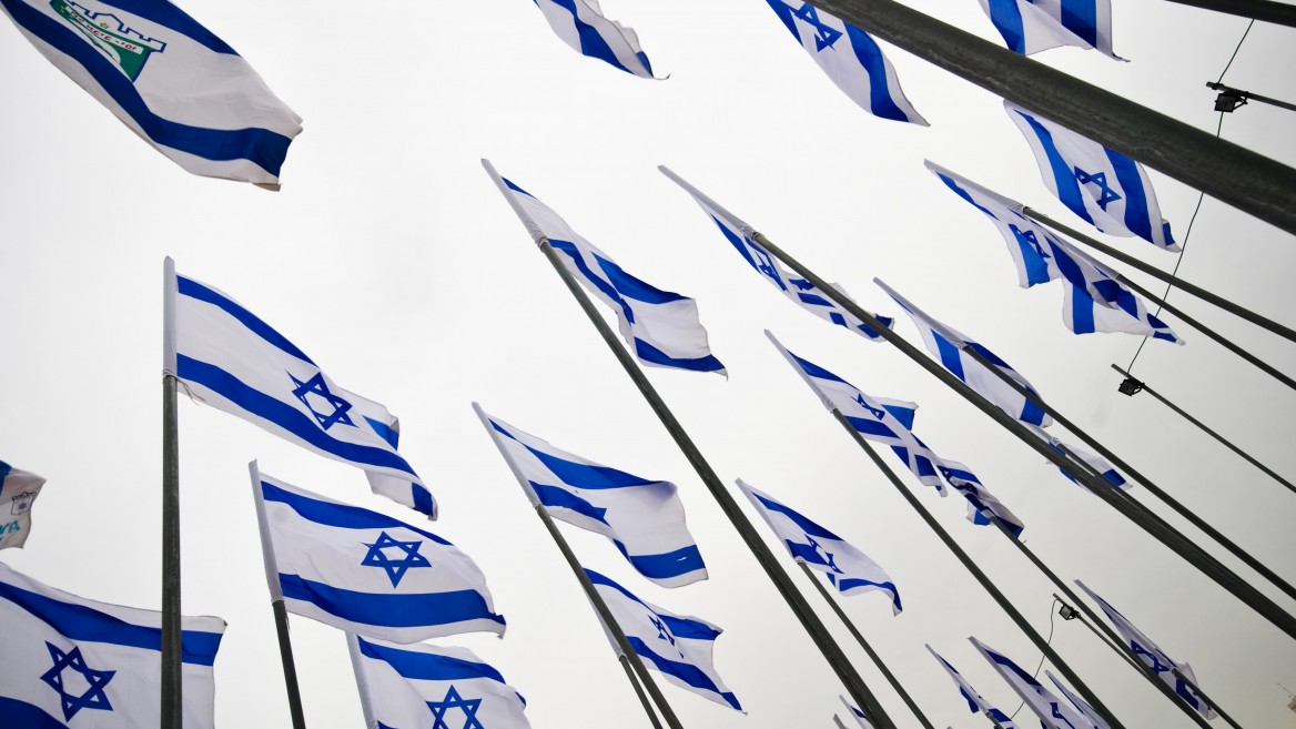 Israeli flags flutter in the wind in celebration of the country's 65th anniversary. (Shutterstock.com)
