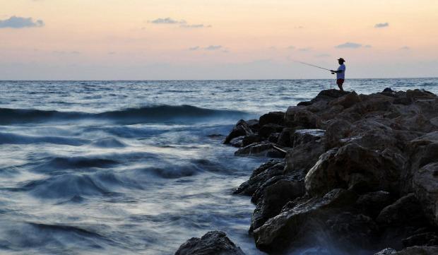 Fishing at the Blue Flag beach Dado in Haifa. Photo by Flash90.