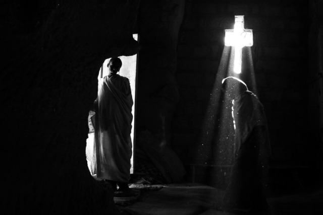 Light catches a crucifix in a church in Lalibela, as an Ethiopian pilgrim stands at the entrance. Photo by Gali Tibbon