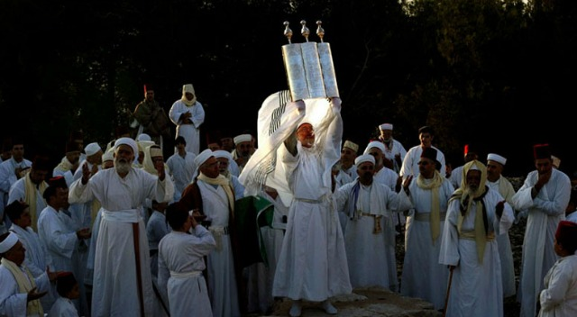 A senior priest of the tiny ancient Samaritan sect holds a Torah during the pilgrimage for the holiday of Tabernacles (Sukkot). Photo by Gali Tibbon