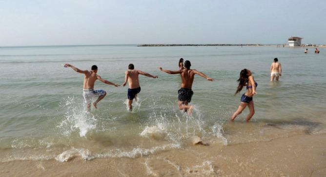 Enjoying the surf at Sironit Beach in Netanya. Photo by Flash90.
