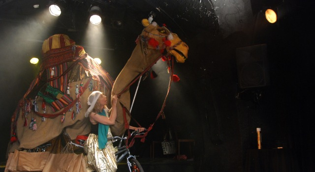 "Sarah Brown with Yakin's giant camel in ""Shooting Stars in Jordan."""