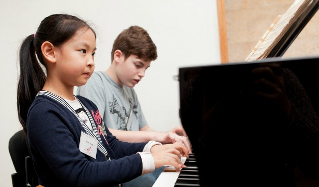 Serena Wang, 8 and Alon Karib, 13, playing piano together at the Chinese-Israel Joint Master Class for Outstanding Young Pianists at the Jerusalem Music Center. Photo by Yael Ilan