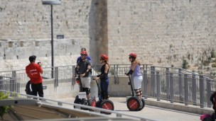 Tourists pause for a photograph as they ride through the Old City of Jerusalem. Photo by Flash90.