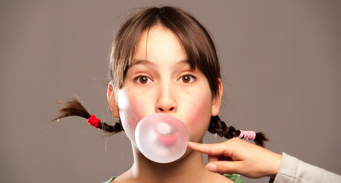 Pop that gum-chewing habit to lessen headaches. Image via Shutterstock.com