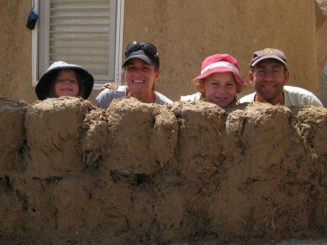 An American family mud building on Kibbutz Lotan as part of the Go-Eco voluntouring program.