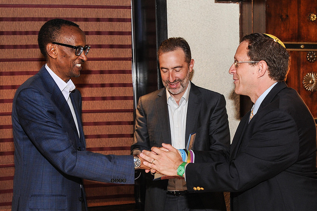 Rwandan President Paul Kagame shakes hands with Yosef Abramowitz, president of Gigawatt Global and CEO of Energiya Global, in Jerusalem. Start-Up Nation co-author Saul Singer stands behind them.