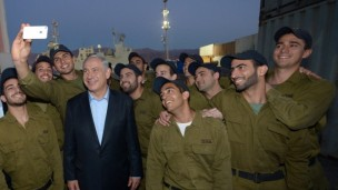 Prime Minister Benjamin Netanyahu poses for a selfie with IDF soldiers.   (Haim Zach/ GPO/Flash90)
