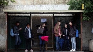 pupils are waiting in a bus stop