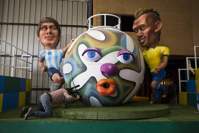 An Israeli worker works on figures depicting Argentine soccer player Lionel Messi and Brazilian player Neymar as part of the preparations for the Holon Adloyada parade on March 16. Photo by Yonatan Sindel/Flash90