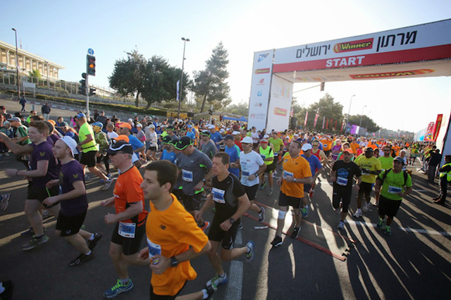 Runners take in Jerusalem's sights during the Marathon in 2014.