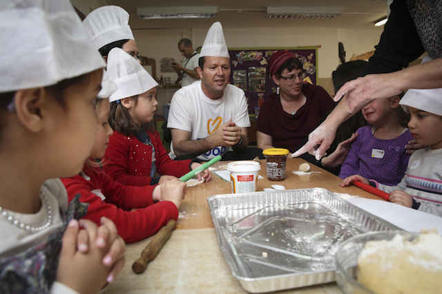 "Jerusalem Mayor Nir Barkat makes hamentschen for soldiers with kindergartners on March 11, ""Good Deeds Day"" in Israel. Photo by Hadas Parush/Flash90"