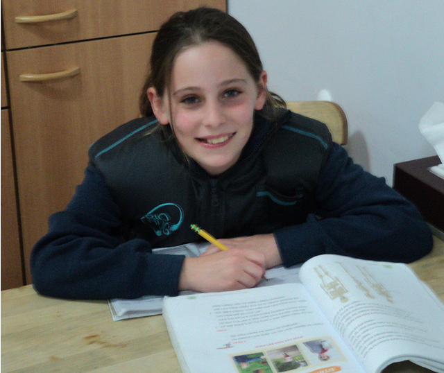 A child doing homework while wearing the BioHug.