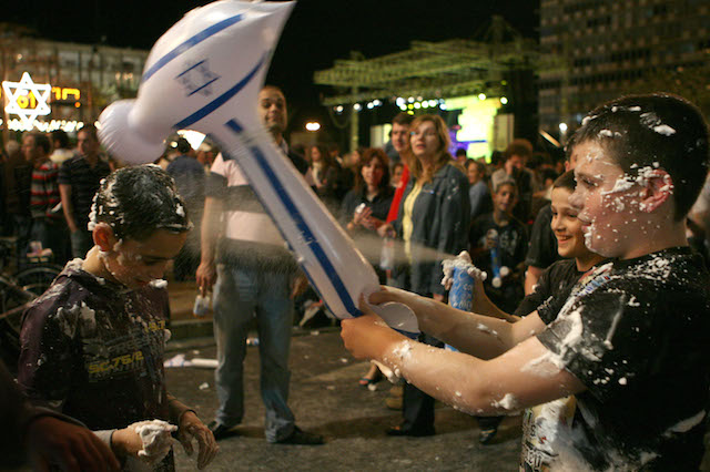 Children celebrating Israeli Independence Day in Rabin Square in Tel Aviv, blow-up hammers in hand. Photo by Liron Almog/Flash90