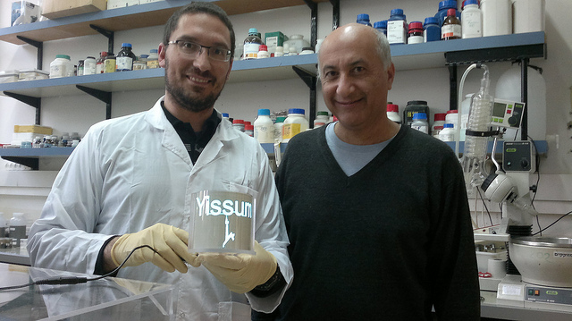 Magdassi with graduate student Alon Shimoni and the lamp lit with conductive nanoparticles. Photo by Abigail Klein Leichman