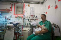 A nurse cares for a newborn in a shelter at Barzilai as a warning siren sounds for possible incoming rockets in Asheklon. Photo by Uri Lenz/FLASH90