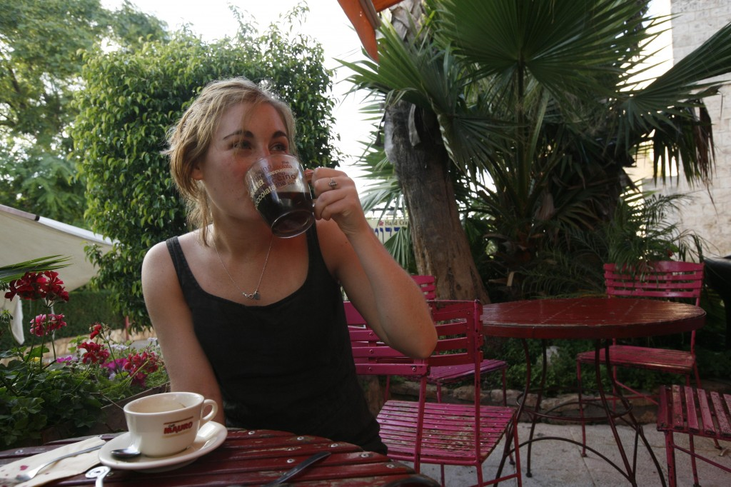 A young woman drinks coffee at a cafe in Tel Aviv. Photo by Flash90.