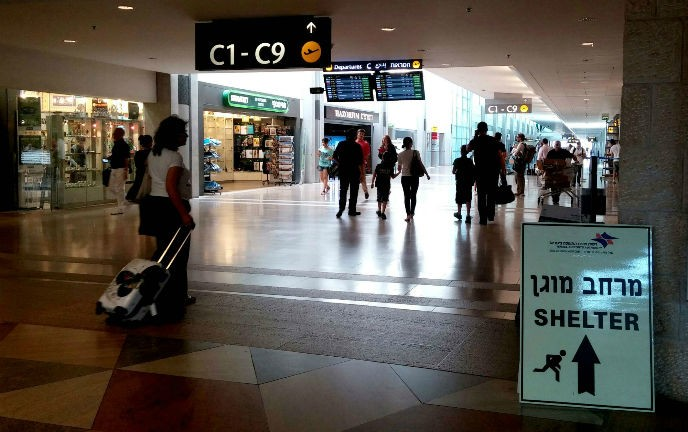 Signs at the Ben-Gurion Airport point visitors to a bomb shelter. Photo by Tzahi Ben Ami/FLASH90.