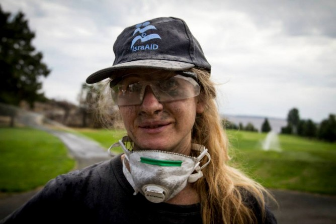 An IsraAID volunteer sifting through ashes in Washington State.
