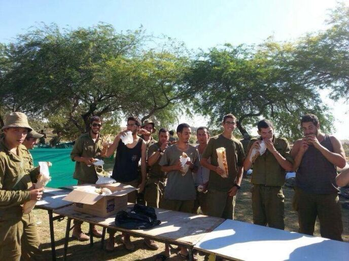 Soldiers enjoying their free sandwiches.