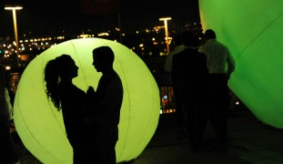 A young couple silhouetted at Jerusalem's Light Festival. Photo by Mendy Hechtman/FLASH90