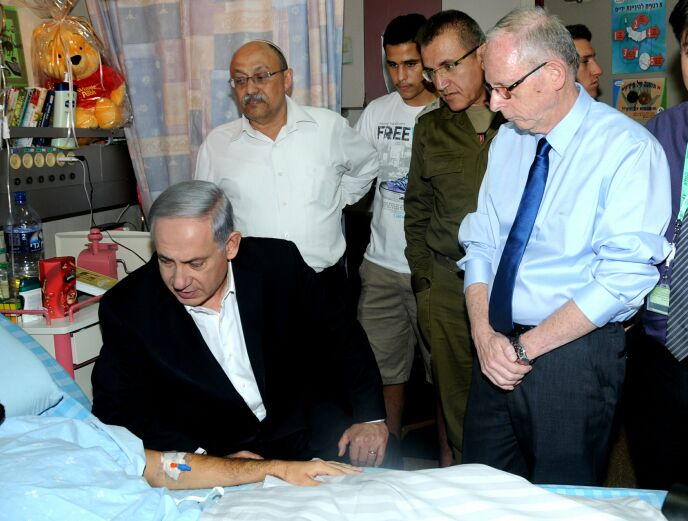 Soroka Director Ehud Davidson, right, with Prime Minister Netanyahu at the bedside of a wounded soldier. Photo courtesy of Soroka Medical Center