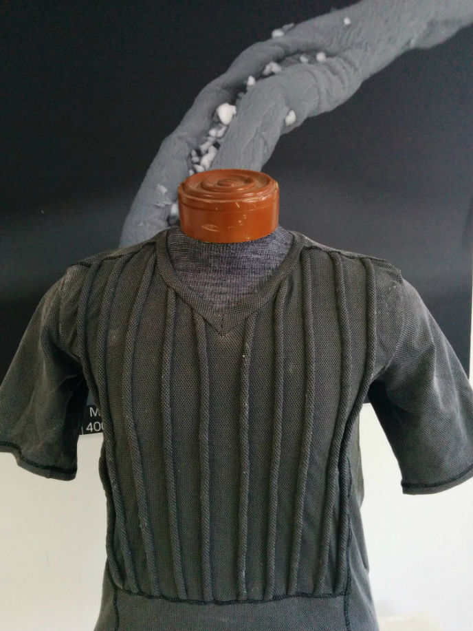 "A sample shirt developed by Argaman for the Japanese police and racecar drivers. It controls core body temperature to reduce heart stress; can deliver active ingredients to sterilize a wound and promote healing; has ""weltings"" to keep a bulletproof vest off the body to allow air circulation; and is fire retardant."