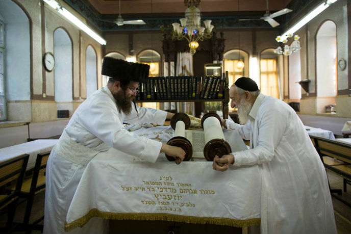 Ultra Orthodox men roll a Torah scroll in Mea Shearim a few hours before the start of Yom Kippur. (Yonatan Sindel/Flash90)