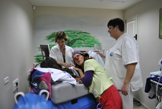 Medical clown Shoshi Ofir working with the medical staff and a young patient at the Tene Center.