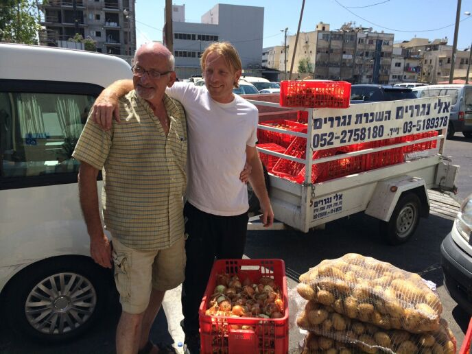 Gideon Ben-Ami and his son Doron loading produce into the van.