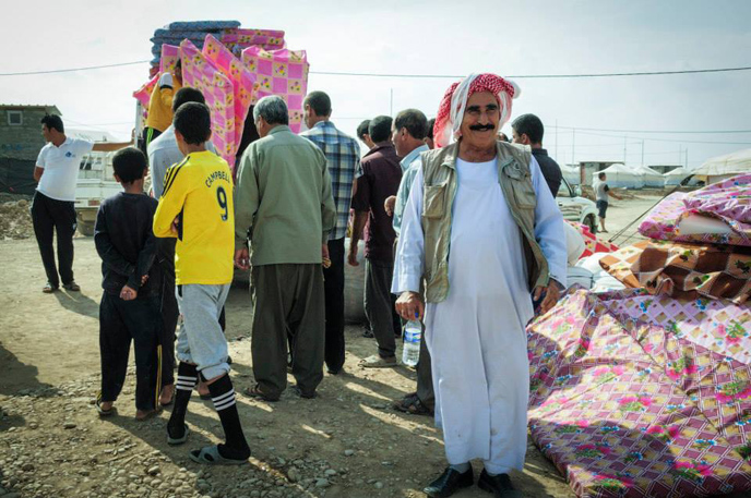Newly-arrived Yazidi families receive emergency supplies at a make-shift distribution point. (IsraAID)