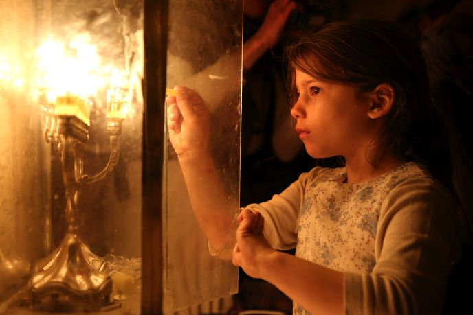 A girl lighting a hanukkiyah outside her home in Jerusalem's Nachlaot neighborhood (Hadas Parush/FLASH90)