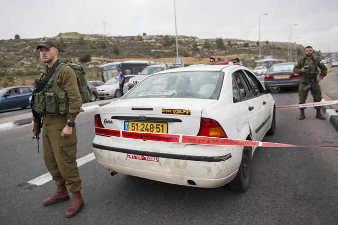IDF soldiers stand guard at the scene of a terror attack on December 12, 2014. (Photo by Yonatan Sindel/Flash90)