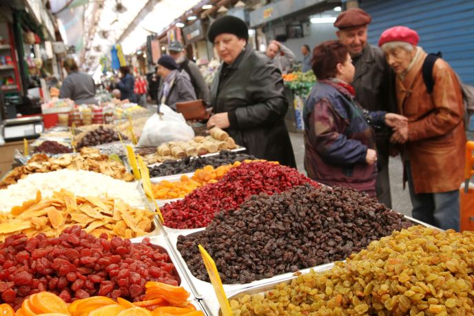 Customers choosing dried fruits for sale at the Machane Yehuda market in Jerusalem in preparation for the Jewish holiday of Tu B'Shevat. Photo by Miriam Alster/FLASH90