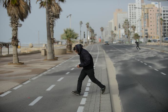 A man runs against sandy winds in Tel Aviv on January 6, 2014. Photo by Ben Kelmer/Flash90