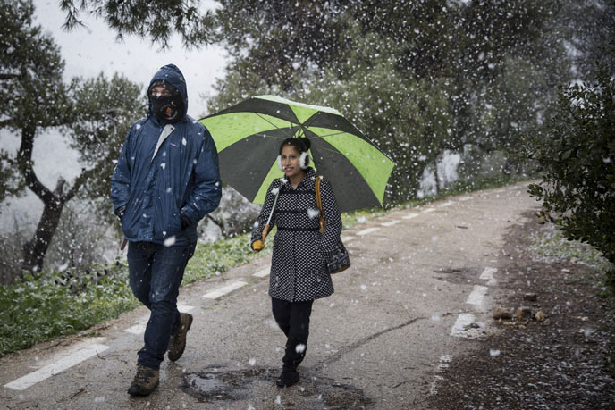 A couple seen walking through Sacher Park in Jerusalem on a snowy day. (Photo by Hadas Parush/Flash90)