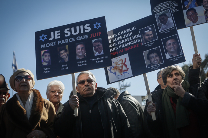 Mourners held signs with pictures of the four Jewish victims in the Paris Kosher Market terror attack. (Photo by Miriam Alster/Flash90)