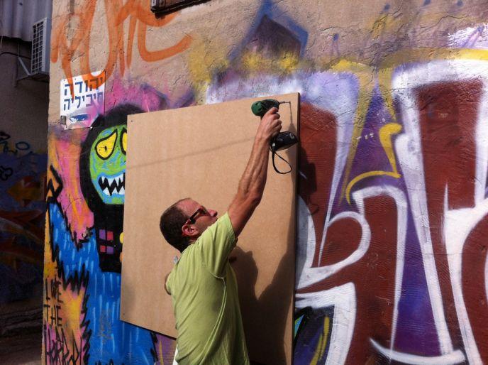 Eran Shimshovic mounting a blank board in Florentin.