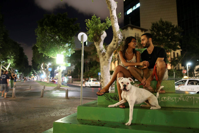 A young couple take a moment to relax with their dog on Rothschild Avenue in Tel Aviv in the midst of last summer's Operation Protective Edge, when Code Red alert sirens sounded frequently in the city warning of incoming rockets fired from Gaza. Photo by Nati Shohat/Flash90